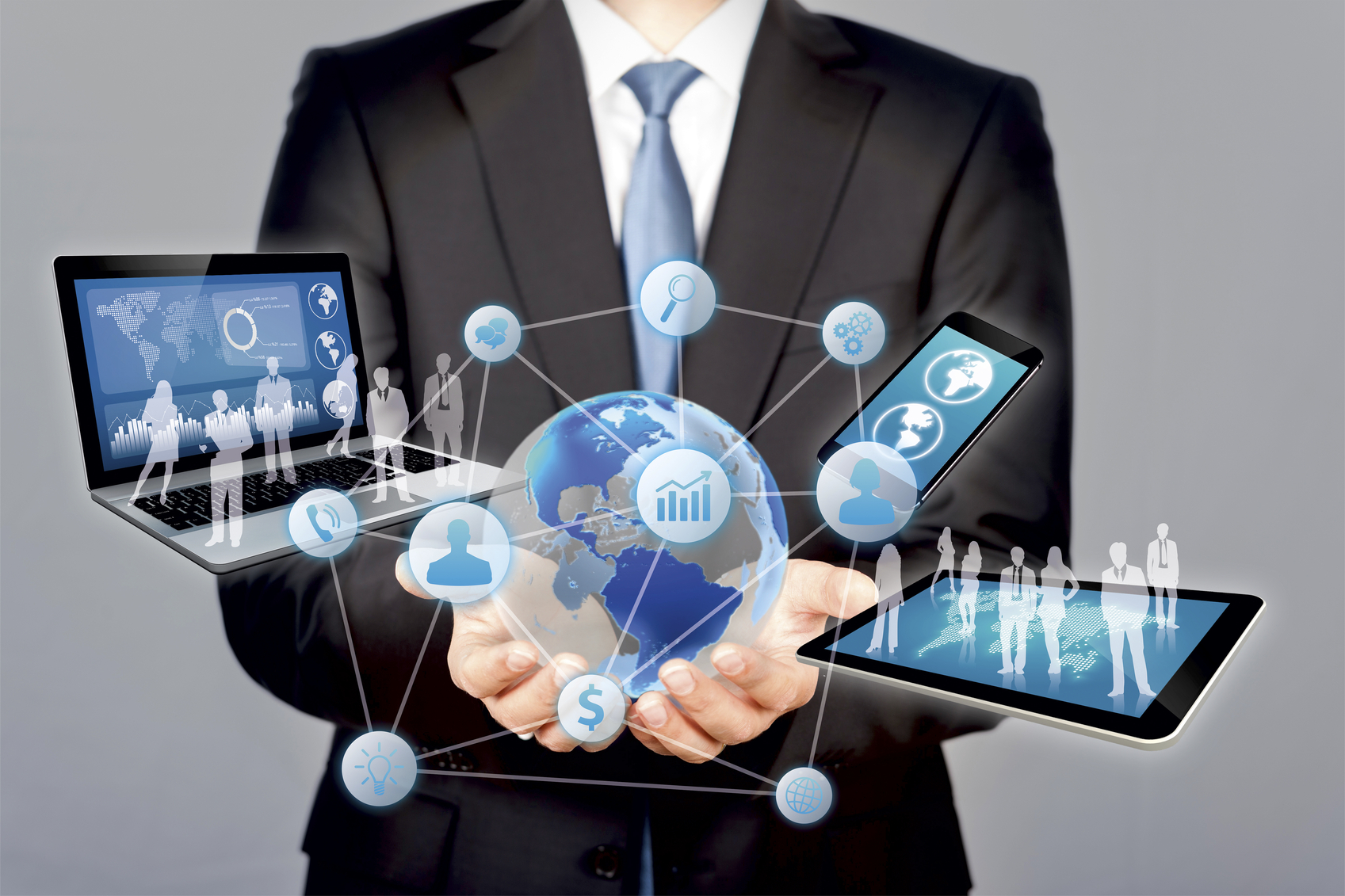 The image displays an individual dressed in a suit with several pieces of technology extending from his hands in a cloud formation.